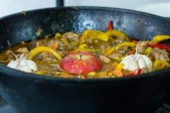 肉用土豆、苹果和大蒜在一口大锅在火 免版税库存照片