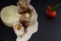 肉用调味汁和蘑菇在土豆泥旁边在黑背景 库存照片