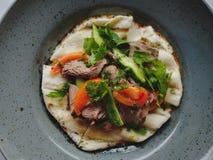 肉盘的宏观图片在蓝色板材背景的 新鲜的沙拉用牛肉、蕃茄、黄瓜和pitta面包 免版税库存照片