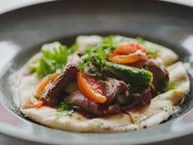 肉盘的宏观图片在蓝色板材背景的 新鲜的沙拉用牛肉、蕃茄、黄瓜和pitta面包 库存照片