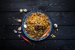 肉饭和成份在板材有东方装饰品的在黑暗的木背景 中亚烹调- Plov顶视图 图库摄影