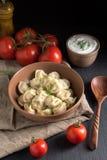 肉饺子服务与在黑石背景的酸性稀奶油 库存图片
