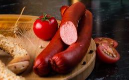 肉香肠和蕃茄,椒盐脆饼,麦子耳朵 免版税库存图片