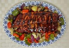 肋骨机架烹调了与烤肉汁和烘烤菜 库存照片