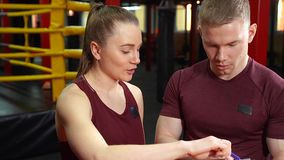 肌肉个人教练写在剪贴板和谈论训练计划对年轻女人在交叉训练健身房 股票录像