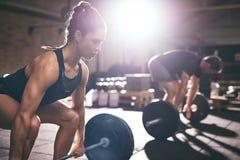 肌肉举重的杠铃的男人和妇女 免版税库存图片