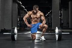 肌肉人解决在健身房的,爱好健美者 强的男性赤裸躯干吸收 免版税图库摄影