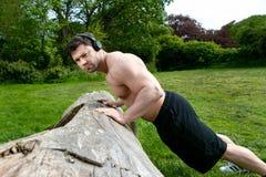 肌肉人,佩带的耳机训练与pressups反对一棵下落的树在公园 免版税库存照片