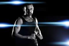 肌肉人,在拳头的钩子手,在竞技场,在聚光灯的强光附近 库存照片