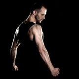 肌肉人,在拳头,黑背景的钩子手 图库摄影