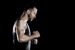 肌肉人,在拳头,黑背景,文本的地方的钩子手在右边 图库摄影