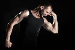 肌肉人,展示他的二头肌,黑背景 库存照片