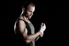肌肉人,栓在他的手上的有弹性绷带,黑背景 图库摄影