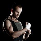肌肉人,栓在他的手上的有弹性绷带,黑背景 免版税图库摄影