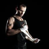 肌肉人,栓在他的手上的有弹性绷带,黑背景 免版税库存图片