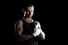 肌肉人,栓在他的手上的有弹性绷带,黑背景 免版税库存照片