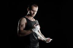 肌肉人,栓在他的手上的有弹性绷带 免版税库存图片