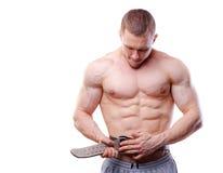 肌肉人紧固在白色的举的传送带 免版税库存照片