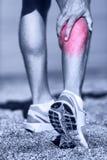 肌肉伤-供以人员抓住小牛肌肉的赛跑 免版税库存图片