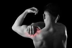 年轻肌肉体育人在痛苦中的拿着疼痛肩膀接触按摩在锻炼重音 免版税库存照片