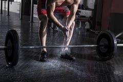 肌肉在杠铃worko前的运动员拍的手特写镜头  图库摄影