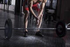 肌肉在杠铃worko前的运动员拍的手特写镜头  免版税库存照片