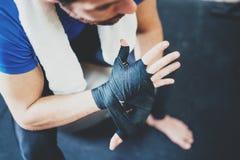 肌肉坚硬kickboxing的训练的拳击手人prepairing的手在健身房 栓黑拳击的年轻运动员 库存照片