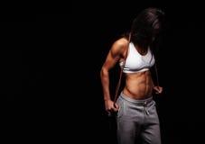 肌肉女性摆在与跳绳 库存照片