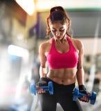 肌肉妇女训练在健身房 免版税库存图片