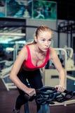 肌肉少妇解决在锻炼脚踏车的在健身房,强烈的心脏锻炼 库存图片