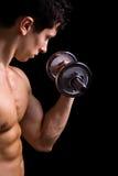 肌肉年轻人增强的哑铃 库存图片