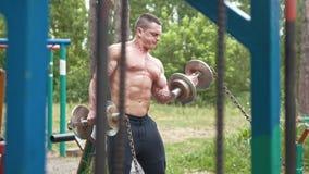 肌肉年轻人采摘重的哑铃在体育在森林里停放 股票录像