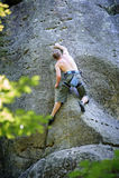 肌肉攀岩运动员在有绳索的峭壁墙壁上上升 库存照片