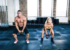肌肉男人和做与水壶球的适合妇女锻炼 图库摄影
