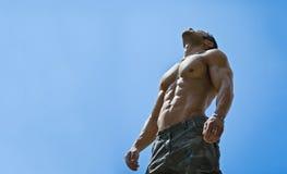 肌肉男性爱好健美者赤裸上身在蓝天 图库摄影