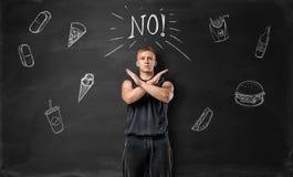肌肉的年轻人陈列停车牌用他的手和对在黑板背景的不健康的食物说不  库存图片