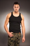 肌肉英俊的人在黑衬衣和长裤地形 图库摄影