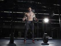 肌肉赤裸上身的在杠铃锻炼前的人拍的手 免版税图库摄影
