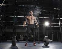 肌肉赤裸上身的在杠铃锻炼前的人拍的手 免版税库存照片