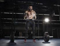 肌肉赤裸上身的在杠铃锻炼前的人拍的手 免版税库存图片