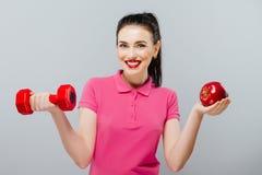 肌肉年轻亚洲妇女手的训练和苹果有红色哑铃的, kg 库存图片