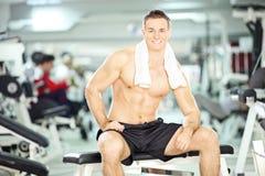 肌肉年轻人坐在健身房的一条长凳 免版税库存照片