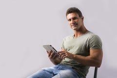 肌肉年轻人坐从ebook设备的椅子读书 库存照片