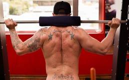 肌肉年轻人执行的杠铃蹲,一个腿的最佳的体型锻炼 图库摄影