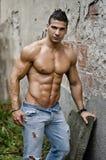 肌肉年轻拉丁美州的人赤裸上身在倾斜在墙壁的牛仔裤 图库摄影