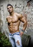 肌肉年轻拉丁美州的人赤裸上身在混凝土墙前面的牛仔裤 库存图片
