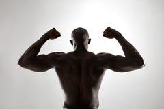 肌肉man& x27; 在剪影的s后面 免版税图库摄影