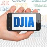 股市标注概念:拿着有DJIA的手智能手机在显示 免版税库存图片