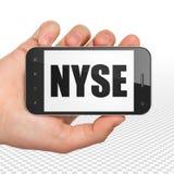 股市标注概念:拿着有NYSE的手智能手机在显示 免版税库存图片