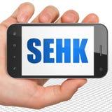 股市标注概念:拿着有SEHK的手智能手机在显示 免版税库存照片